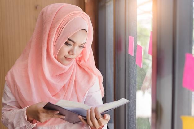 Schöne junge moslemische frau, die ein buch vor glaswandbüro liest. Premium Fotos