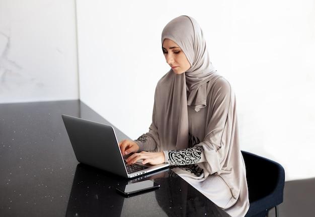 Schöne junge muslimische frau, die hijab trägt und zu hause mit laptop arbeitet Premium Fotos