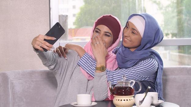 Schöne junge muslimische mädchen machen selfie auf einem smartphone Premium Fotos