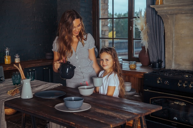 Schöne junge mutter, die zu hause spaß mit ihrer kleinen netten tochter in einem dunklen kücheninnenraum spielt und hat Premium Fotos
