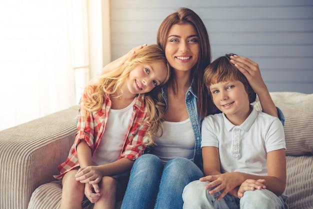 Schöne junge mutter und ihre kinder umarmen. Premium Fotos