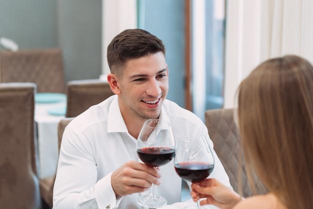 Schöne junge paare mit gläsern rotwein im luxusrestaurant Premium Fotos