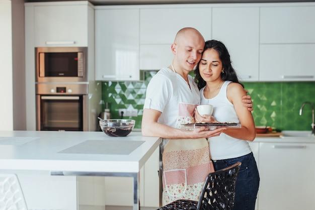 Schöne junge paare stellten das lächeln beim in der küche zu hause kochen grafisch dar. Premium Fotos