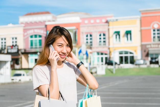 Schöne junge shopaholic asiatin, die smartphone für die unterhaltung verwendet Kostenlose Fotos