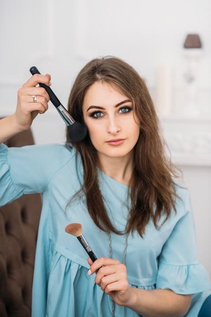 Schöne junge stilvolle frau mit make-up-bürsten in den händen Premium Fotos
