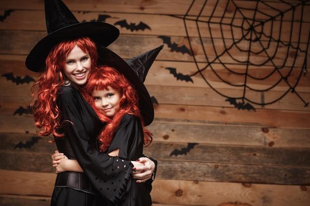 Schöne kaukasisch mutter und ihre tochter mit langen roten haaren in hexenkostüme feiern halloween posiert Premium Fotos