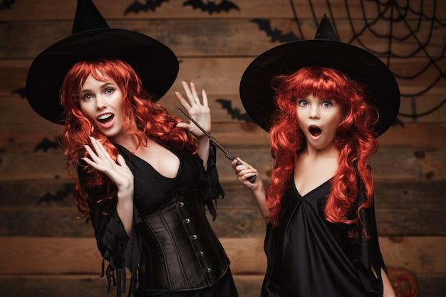 Schöne kaukasisch mutter und ihre tochter mit langen roten haaren in hexenkostümen und zauberstab feiert halloween posiert Premium Fotos