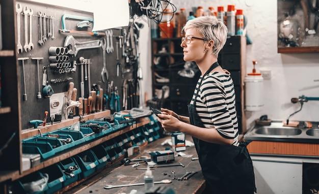 Schöne kaukasische arbeiterin mit kurzen blonden haaren und brillen, die werkzeug von der wand nehmen, um fahrrad zu reparieren. innenraum der fahrradwerkstatt. Premium Fotos