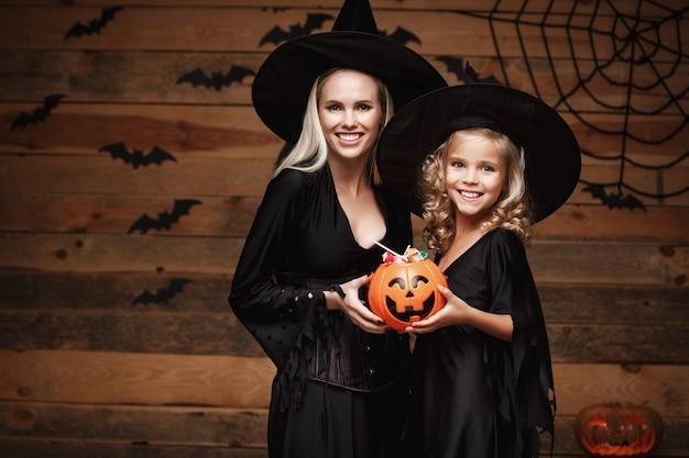 Schöne kaukasische mutter und ihre tochter in hexenkostüme halloween feiern mit teilen halloween süßigkeiten Premium Fotos
