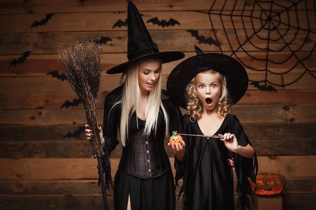 Schöne kaukasische mutter und ihre tochter in hexenkostümen genießen magie mit zauberstab zu halloween kürbisglas verwenden Premium Fotos