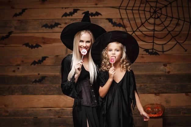 Schöne kaukasische mutter und ihre tochter in hexenkostümen halloween mit halloween süßigkeiten zu feiern Premium Fotos