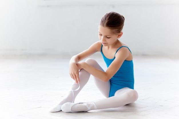 Schöne kleine ballerina im blauen kleid, das sich zu fuß pointe schuhe setzt Kostenlose Fotos