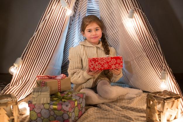 Schöne kleine frau, die mit einem geschenk in seinen händen sitzt Premium Fotos