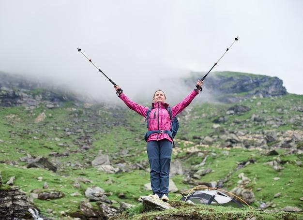 Schöne kletterin, die hände in die luft mit spazierstöcken in händen hebt, während sie auf felsen steht und die schönheit der grünen felsigen nebligen berge bewundert Premium Fotos