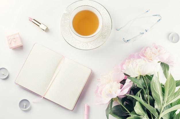 Schöne kosmetik und blumen flach lagen mit notizbuch, kräutertee auf pastellhintergrund. Premium Fotos