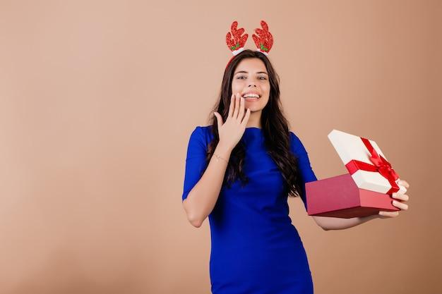 Schöne lächelnde frau, die geschenkbox hält und das lustige weihnachtsband lokalisiert über braun trägt Premium Fotos