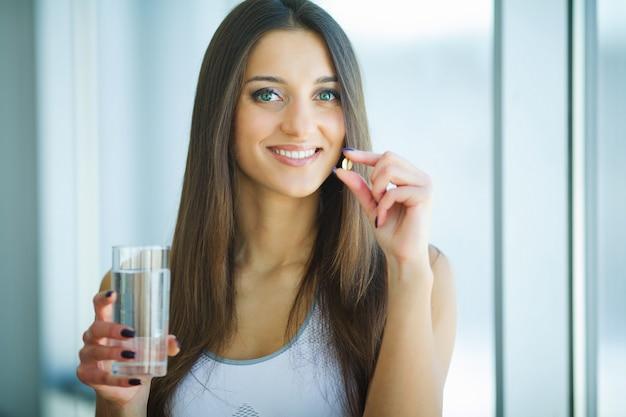 Schöne lächelnde frau, die vitamin-pille einnimmt. nahrungsergänzungsmittel Premium Fotos