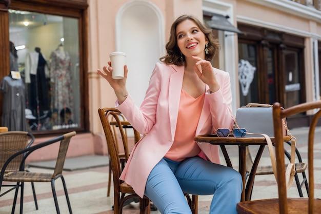 Schöne lächelnde frau im stilvollen outfit, das am tisch sitzt und rosa jacke, romantische glückliche stimmung, datum im café, frühlingssommer-modetrend, kaffeetrinker, fashionista trägt Kostenlose Fotos