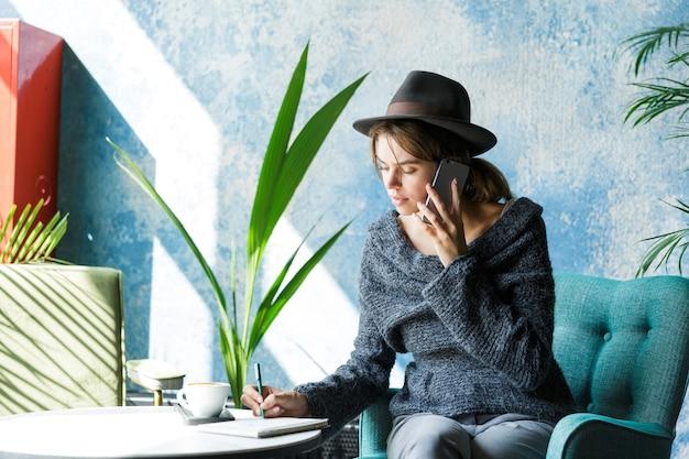Schöne lächelnde junge frau gekleidet in pullover und hut, die im stuhl am kaffeetisch sitzen und auf handy sprechen, stilvolles interieur Premium Fotos