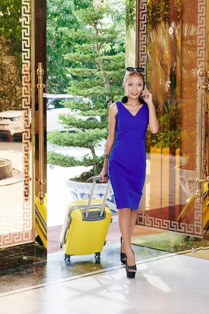 Schöne lächelnde junge frau mit kleinem koffer, der am telefon spricht, wenn er schickes hotel betritt Premium Fotos