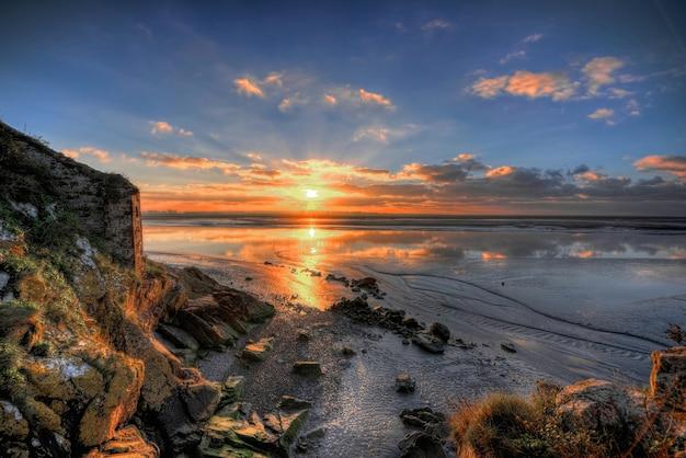 Schöne landschaft des atemberaubenden sonnenaufgangs, der sich im meer spiegelt Kostenlose Fotos
