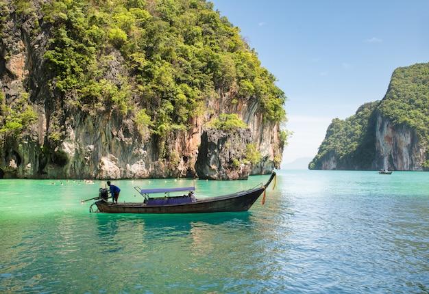 Schöne landschaft des felsenberges und des haarscharfen meeres mit longtailboot in phuket, thailand. Premium Fotos
