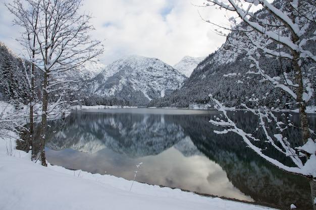Schöne landschaft des plansees, umgeben von hohen schneebedeckten bergen in heiterwang, österreich Kostenlose Fotos