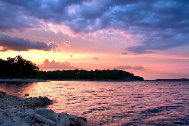 Schöne landschaft des sonnenuntergangs, der sich im meer unter den atemberaubenden bunten wolken spiegelt Kostenlose Fotos