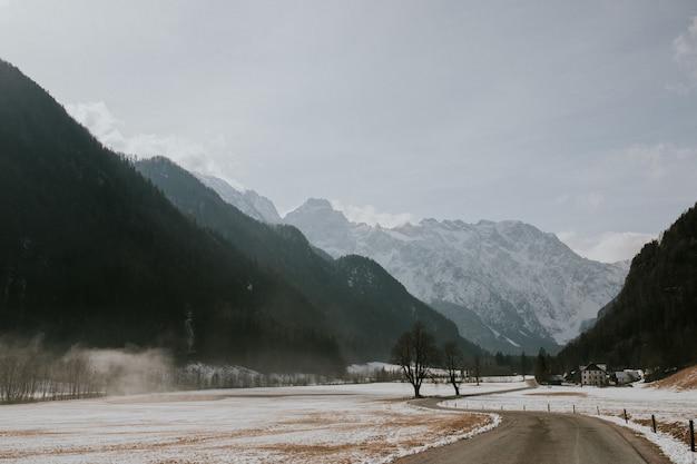 Schöne landschaft einer straße, umgeben von hohen felsigen bergen unter einem bewölkten himmel Kostenlose Fotos