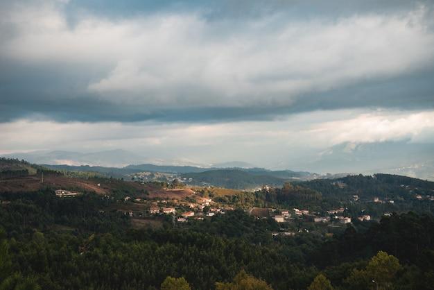Schöne landschaftsaufnahme einer stadt, die unter den bäumen in einer bergigen gegend versteckt ist Kostenlose Fotos