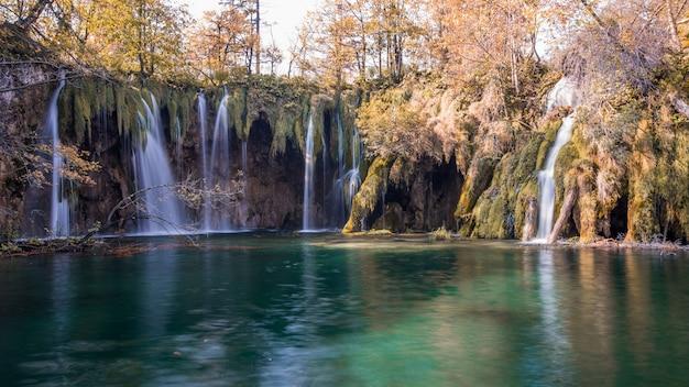 Schöne landschaftsaufnahme eines malerischen sees mit wasserfällen, die in plitvice, kroatien hineinfließen Kostenlose Fotos