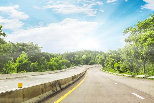 Schöne landstraßenstraße von thailand mit hintergrund des grünen berges und des blauen himmels Kostenlose Fotos