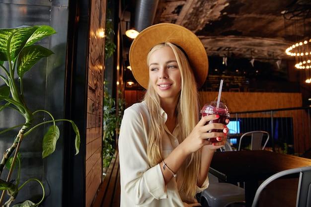 Schöne langhaarige blonde frau gekleidet in stilvolle kleidung, die über restaurantinnenraum sitzt und verträumt aus dem fenster schaut und tasse mit getränk und strohhalm in erhobenen händen hält Kostenlose Fotos