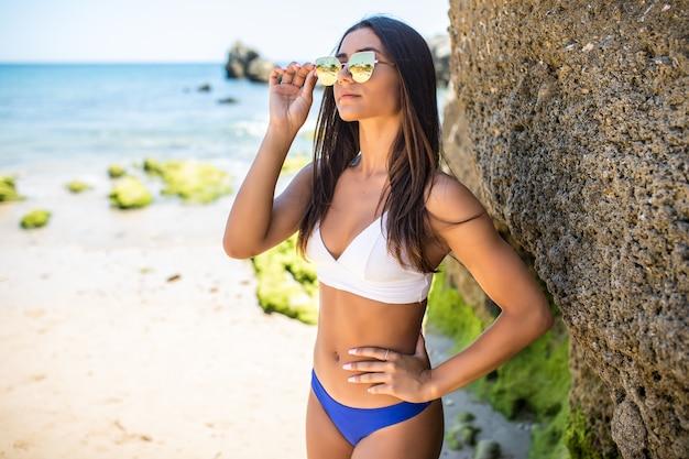 Schöne lateinische frau im bikini auf dem klippenstrand in der ozeanküste. Kostenlose Fotos
