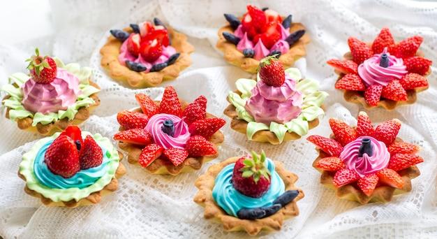 Schöne leckere cupcakes hautnah mit erdbeeren, geißblatt, blauer und rosa creme Premium Fotos