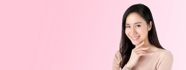 Schöne leuchtende asiatische frau, die mit der hand auf kinn lächelt Premium Fotos