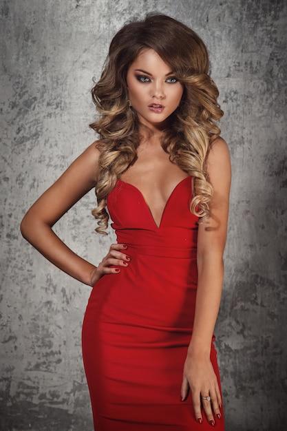 Schöne lockige frau im roten kleid Kostenlose Fotos