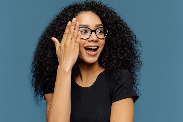 Schöne lockige frau schaut beiseite, berührt gesicht, trägt transparente gläser, schwarzes beiläufiges t-shirt Premium Fotos