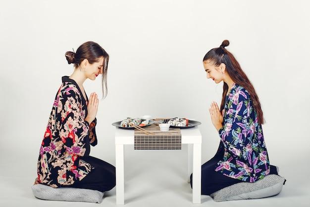 Schöne mädchen, die sushi in einem studio essen Kostenlose Fotos