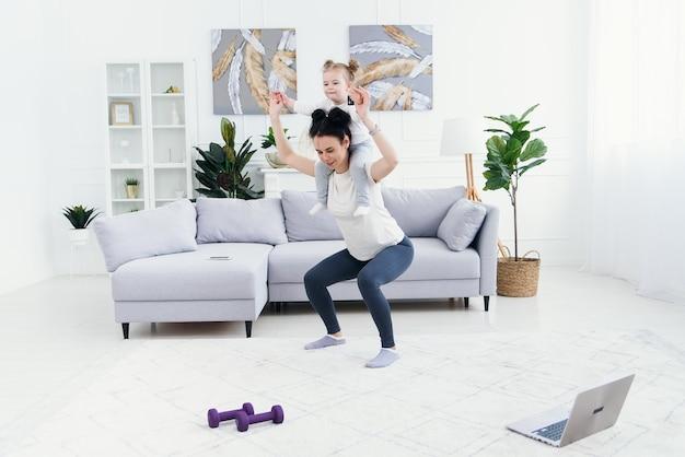 Schöne mama und charmante kleine tochter lächeln, während sie zu hause zusammen fitnessübungen machen. Premium Fotos