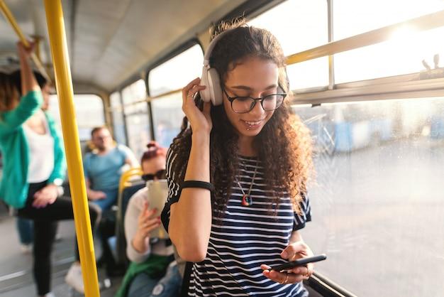Schöne mischlingsfrau, die musik hört, mit smartphone und im öffentlichen verkehr stehend. Premium Fotos
