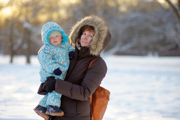 Schöne mittlere greisin und ihr entzückender kleiner enkel am winterpark Premium Fotos