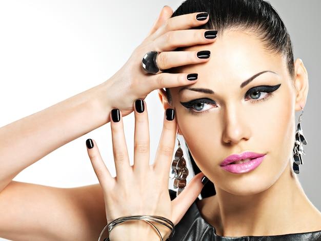 Schöne mode sexy frau mit schwarzen nägeln am hübschen gesicht. hübsches mädchenmodell mit stilvoller bijouterie der silbernen farbe. Kostenlose Fotos