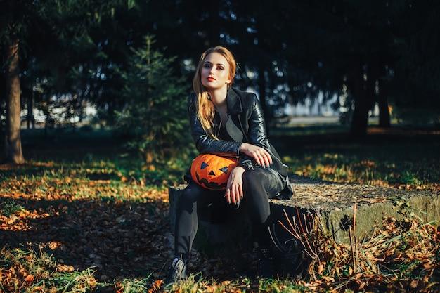 Schöne moderne hexe, die halloween-kürbis im wald hält Premium Fotos
