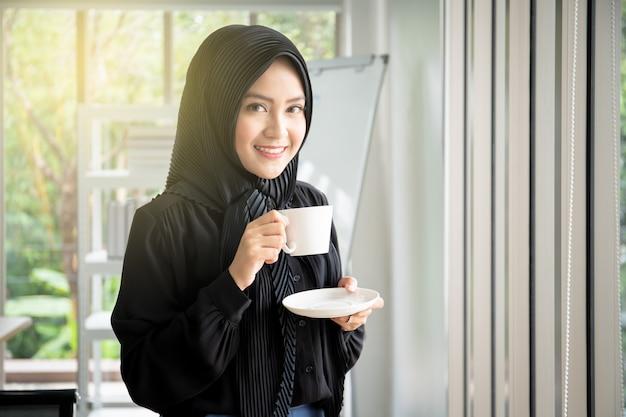 Schöne moslemische geschäftsfrau im schwarzen kleid einen schalenkaffee im büroabschluß oben trinkend. Premium Fotos