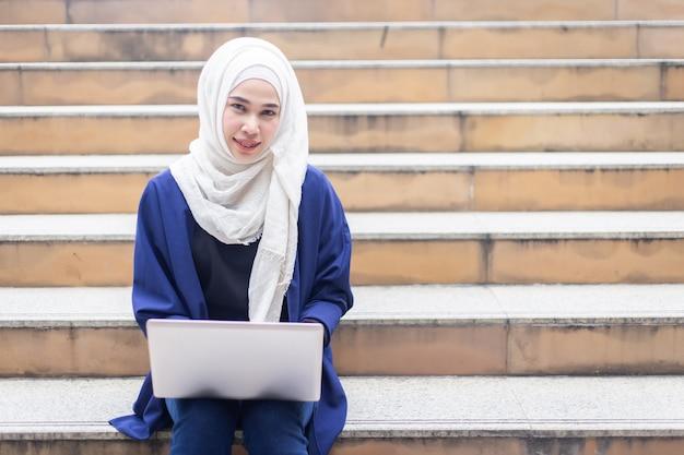 Schöne moslemische geschäftsfrauen im hijab mit dem laptop, der draußen arbeitet. Premium Fotos