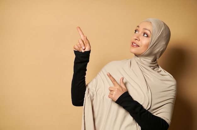 Schöne muslimische frau im hijab, die ihre zeigefinger auf
