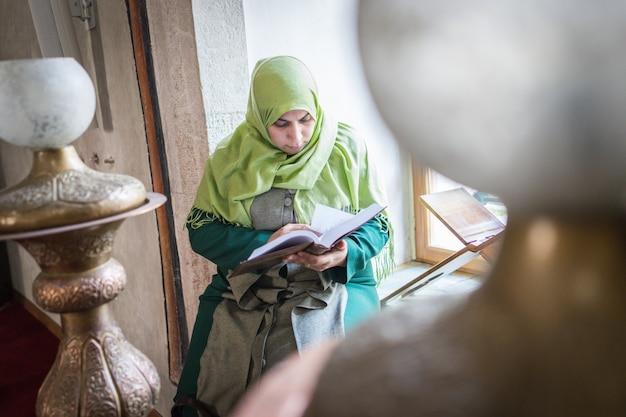 Schöne muslimische junge frau in der moschee, die heiliges buch koran liest Premium Fotos