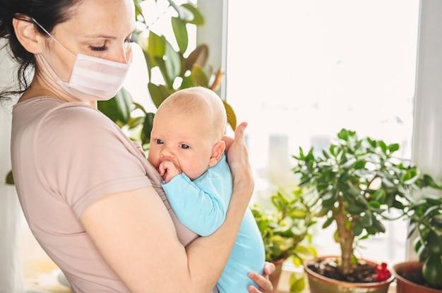 Schöne mutter in der schützenden gesichtsmaske, die ihren kleinen niedlichen neugeborenen sohn hält, der ihn vor viren und infektionen schützt. Premium Fotos