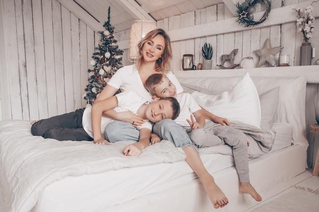 Schöne mutter und ihre zwei kinder, die im weißen skandinavischen artschlafzimmer mit weihnachtsbaum umarmen Premium Fotos
